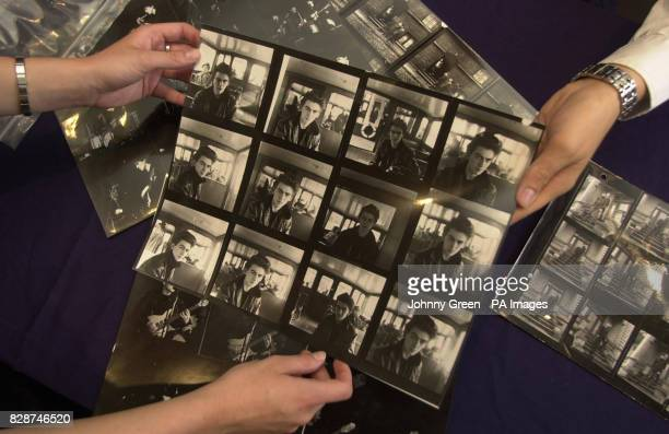 Bonhams staff leaf through contact sheets of George Harrison taken in Hamburg in 1961 at Bonhams auction house in Knightsbridge central London A...
