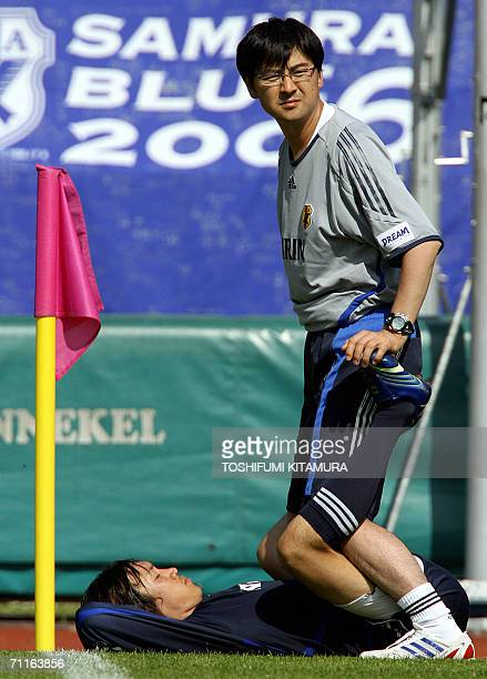 Japanese midfielder Shunsuke Nakamura lies on the ground as he stretches with a trainer after a team training session at the Sports Park North...