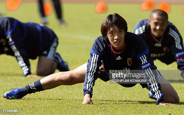 Japanese midfielder Shunsuke Nakamura stretches while Shinji Ono looks on during the morning training session at the Sports Park North stadium in...