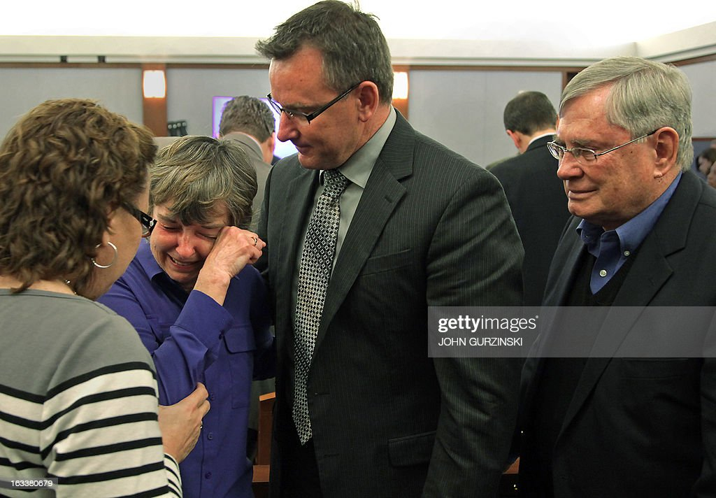 Bonnie Brunson (2nd-L) is comforted by a friend (L), her son Kerry Brunson (2nd-R) and her husband Carl (R) after an emotional testimony Friday, March 8, 2013 in Las Vegas during the trial for the role of Health Plan of Nevada in the largest outbreak of hepatitis C in US history. Brunson is one of the genetically linked patients identified by the CDC and the Southern Nevada Health District. Bonnie Brunson contracted hepatitis C after a colonoscopy at the Endoscopy Center of Southern Nevada. AFP PHOTO / John Gurzinski