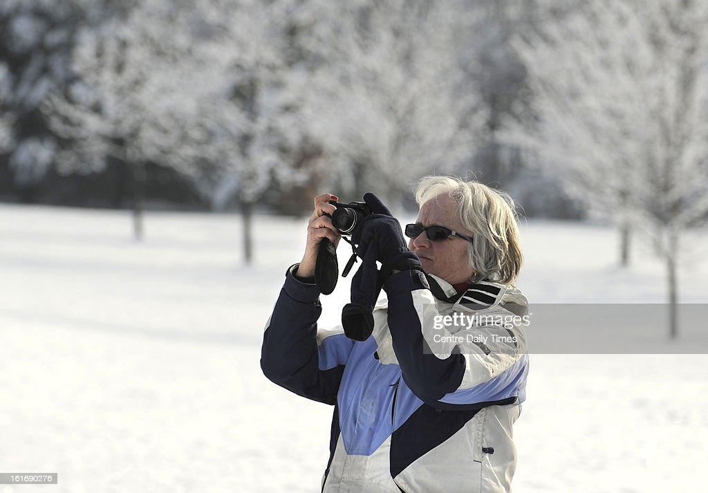 Bonnie Grant walks through Tom Tudek Memorial Park, in State College, Pennsylvania, Thursday, February 14, 2013, taking pictures of the scenic snowfall.