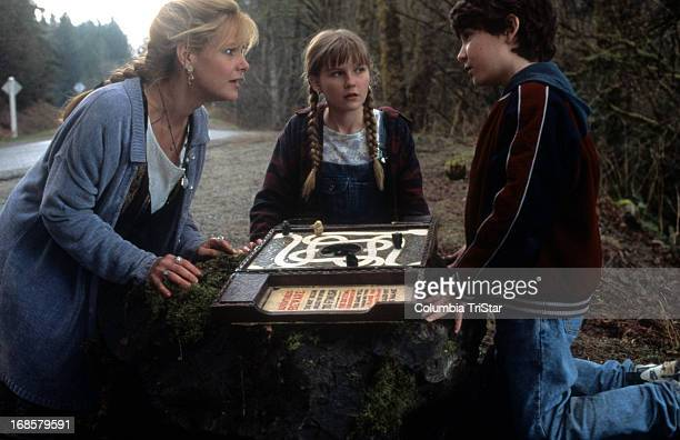 Bonnie Hunt Kirsten Dunst and Bradley Pierce look at the game in a scene from the film 'Jumanji' 1995