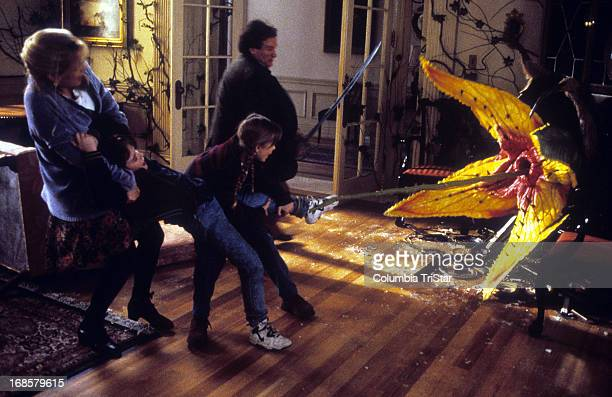 Bonnie Hunt pulls Bradley Pierce as Kirsten Dunst and Robin Williams fight off a flower in a scene from the film 'Jumanji' 1995