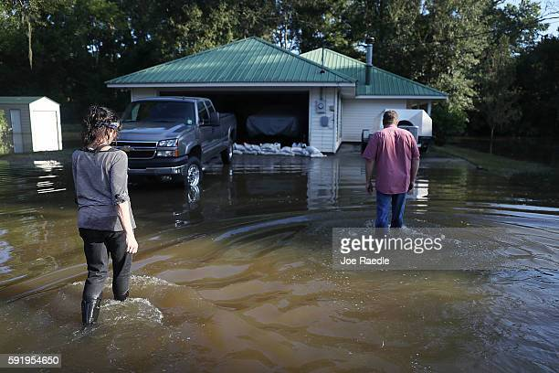 Bonnie Ulmer and Gene Ulme walk to their home to survey the damage after flood waters inundated the home with water on August 19 2016 in St Amant...