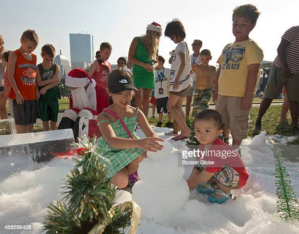 Bonnie Zhang of Ashville NC getting help from Bryan Zhen of Phoenix Ariz building a snowman during Christmas in July at the Outside the box Festival...