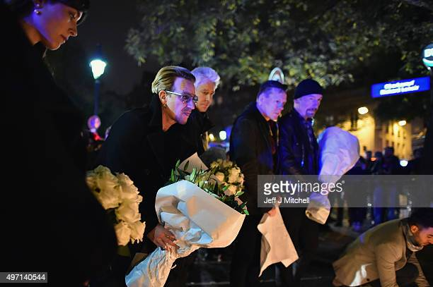 Bono and band members from the band U2 place flowers on the pavement near the scene of yesterday's Bataclan Theatre terrorist attack on November 14...