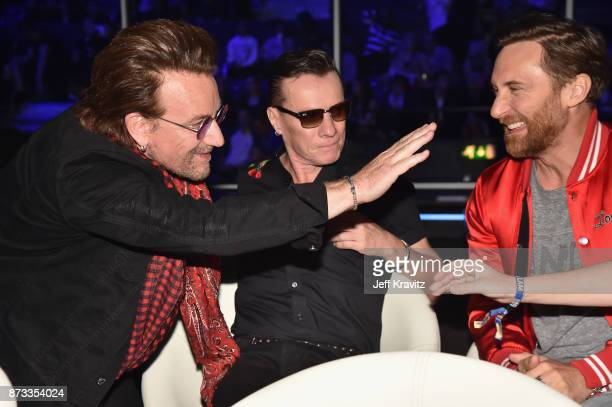 Bono and Larry Mullen Jr of the band U2 sit with David Guetta during the MTV EMAs 2017 held at The SSE Arena Wembley on November 12 2017 in London...