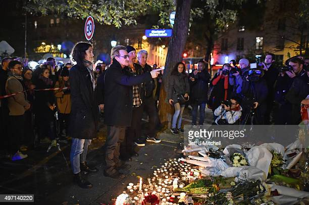 Bono and The Edge of U2 place flowers on the pavement near the scene of yesterday's Bataclan Theatre terrorist attack on November 14 2015 in Paris...