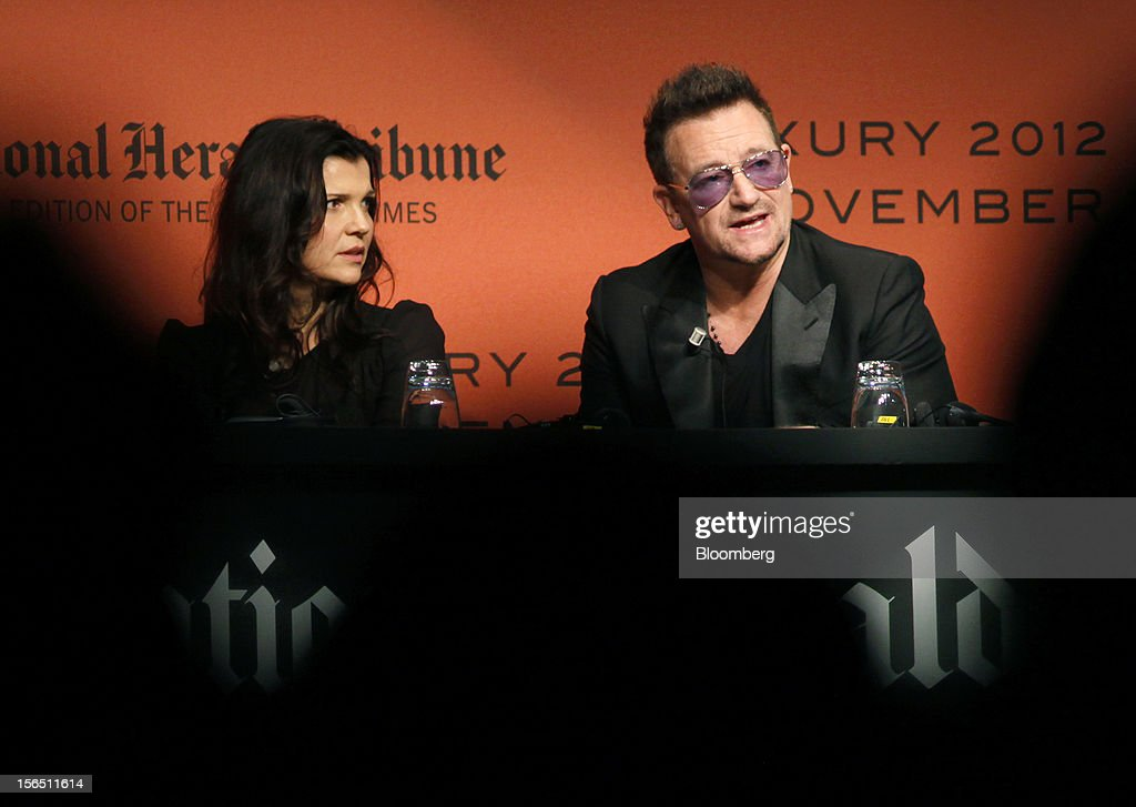Bono, co-founder of the clothing line EDUN, right, speaks as his wife Ali Hewson, co-founder of the clothing line EDUN, listens during the 2012 Luxury Roma conference at the Rome Cavalieri hotel in Rome, Italy, on Friday, Nov. 16, 2012. The euro-area economy succumbed to a recession for the second time in four years as governments imposed tougher budget cuts and leaders struggled to contain the debt crisis that broke out in October 2009. Photographer: Alessia Pierdomenico/Bloomberg via Getty Images