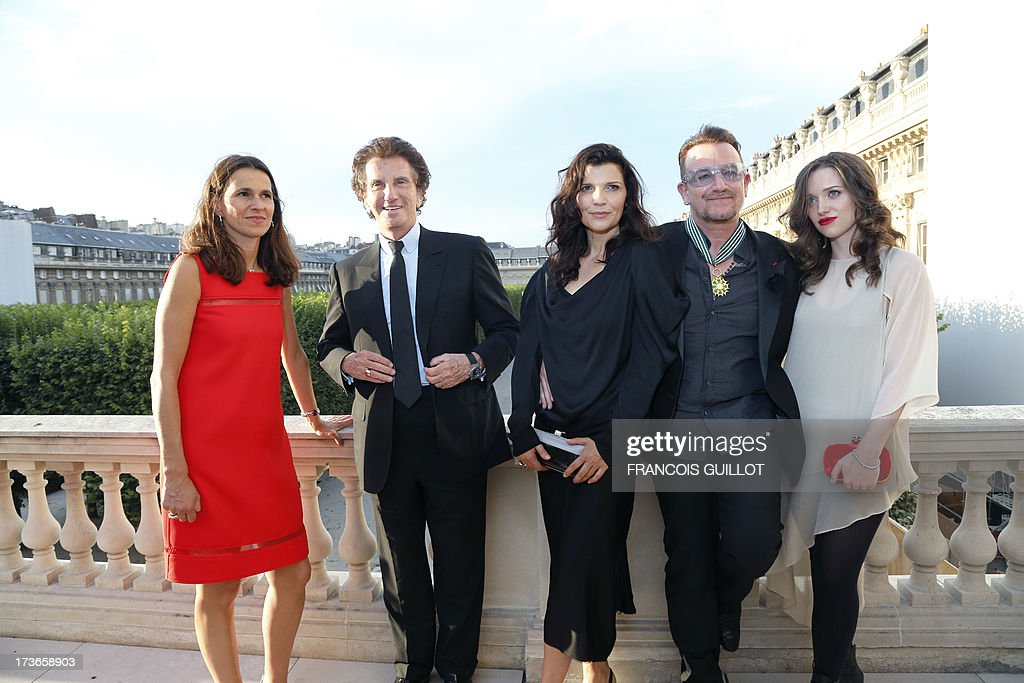 Bono (2R), lead singer of Irish rock band, U2, poses with his wife Ali (C), his daughter Eve Hewson (R), French Culture Minister Aurelie Filippetti (L) and former culture minister, Jack Lang, after receiving the Commander of the Order of Arts and Letters (Commandeur de l'ordre des Arts et des lettres) insignia on July 16, 2013 in Paris.
