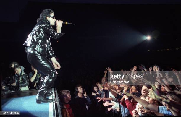 Bono of U2 performs on stage to cheering fans reaching up friom the front rows of the audience at Feyenoord Stadiium on the Zoo TVZooropa Tour De...