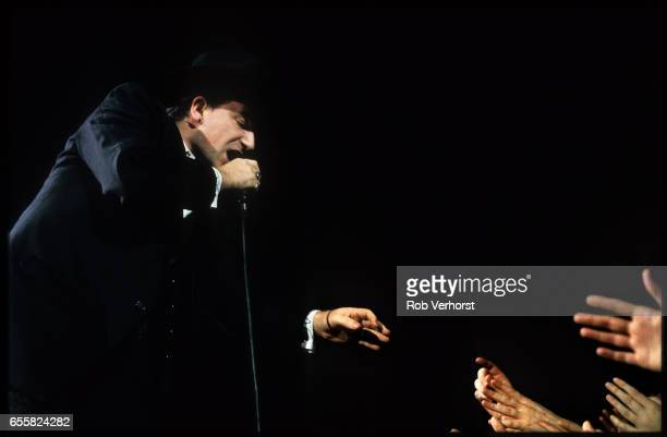 Bono of U2 reaches out hands to the crowd while performing on stage on LoveTown Tour Ahoy Rotterdam Netherlands 7th January 1990