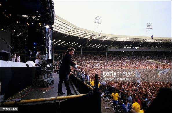 Bono performs on stage during the Live Aid concert at Wembley Stadium on 13 July 1985 in London England Live Aid was watched by millions around the...