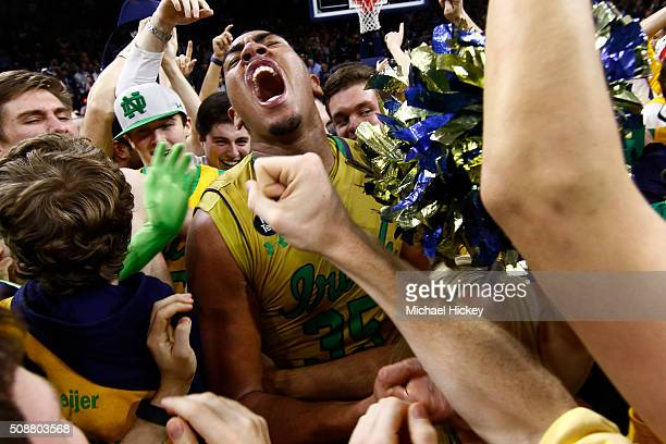 Bonzie Colson of the Notre Dame Fighting Irish celebrates on the court with students after defeating North Carolina Tar Heels at Purcell Pavilion on...