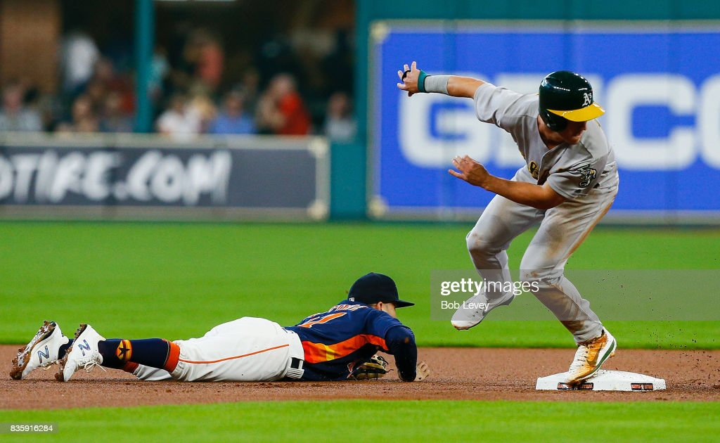 Boog Powell #3 of the Oakland Athletics advances to tthird base after Jose Altuve #27 of the Houston Astros can't handle the throw from Alex Bregman #2 in the first inning and would score on the play at Minute Maid Park on August 20, 2017 in Houston, Texas.