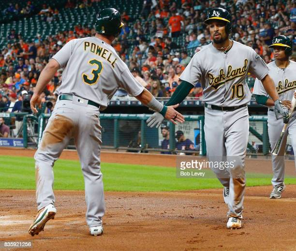 Boog Powell of the Oakland Athletics congratulates Marcus Semien after they scored on two throwing errors in the first inning against the Houston...