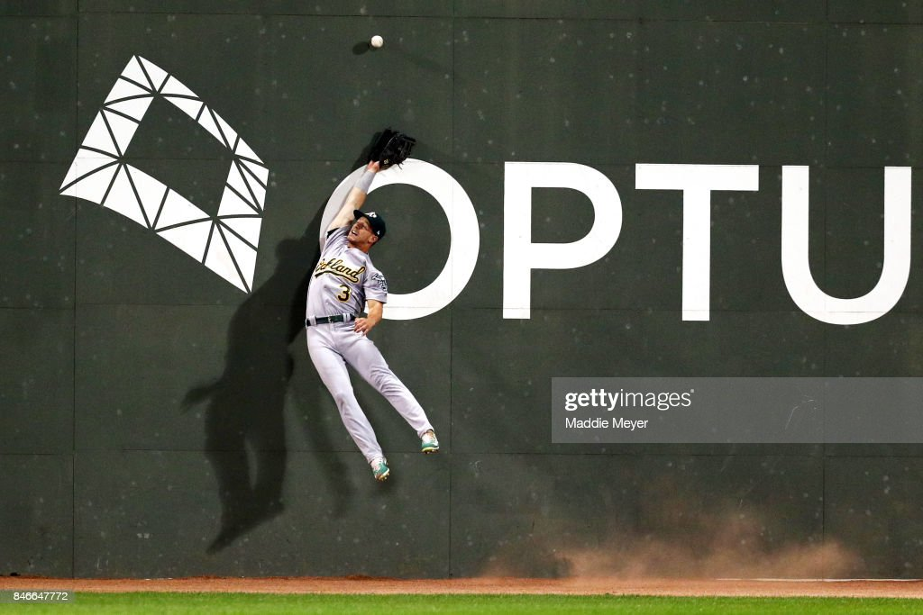 Boog Powell #3 of the Oakland Athletics jumps for a double that was out of reach, hit by Andrew Benintendi #16 of the Boston Red Sox during the third inning at Fenway Park on September 13, 2017 in Boston, Massachusetts.