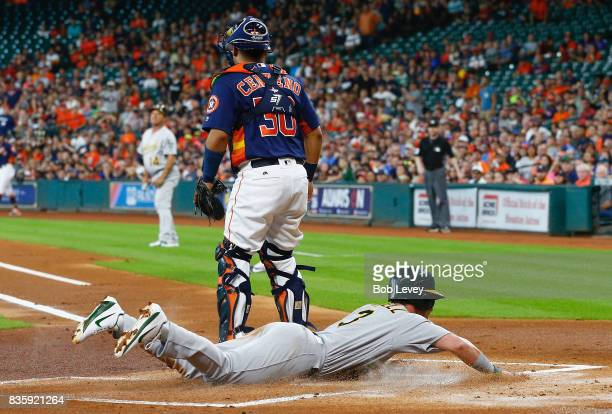Boog Powell of the Oakland Athletics scores in the first inning as he slides behind Juan Centeno of the Houston Astros at Minute Maid Park on August...