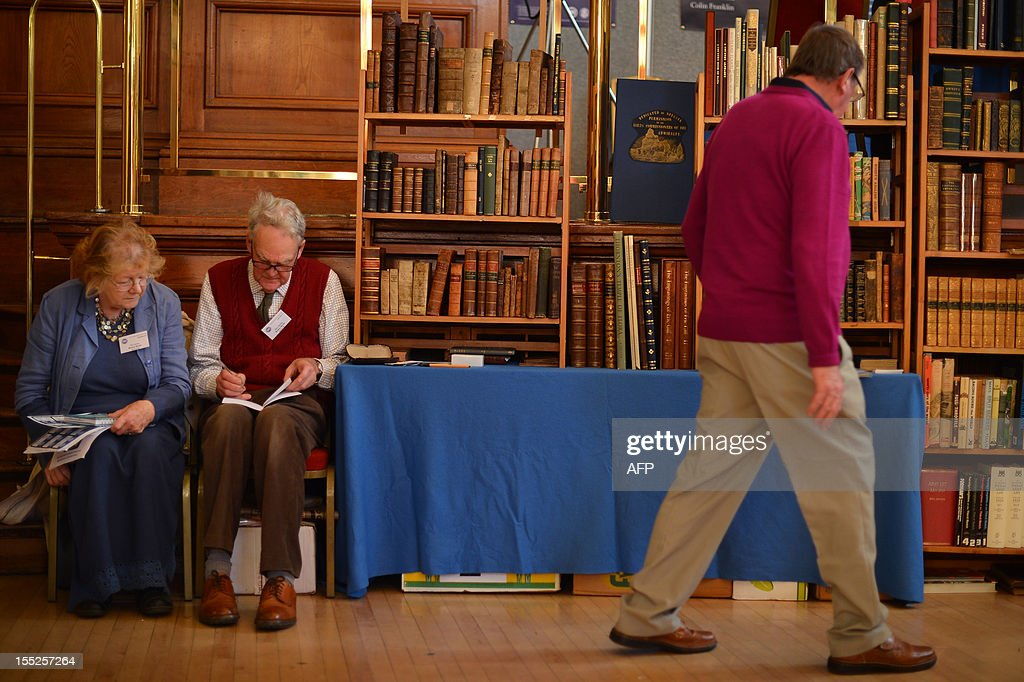 Book a dealer's (L) prepare their Victorian book stall ahead of the opening of the Chelsea Antiquarian Book Fair in London on November 2, 2012. AFP PHOTO / BEN STANSALL