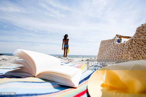 Book and beach bag on sand at beach