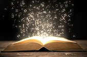 Open book and magical glowing letters.