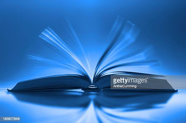 Book fanned open on desk with motion blur between pages