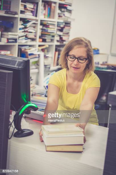 Book lending,  librarian at working table with books