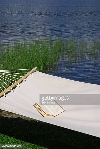 Book lying in hammock, beside lake