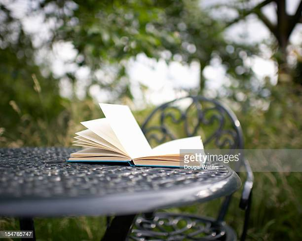 A book on a garden table in the countryside
