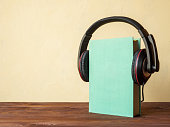 Concept of audiobook. Book on the wooden table with headphones put on them