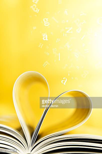 Book pages curled into heart shape, flying letters, yellow background