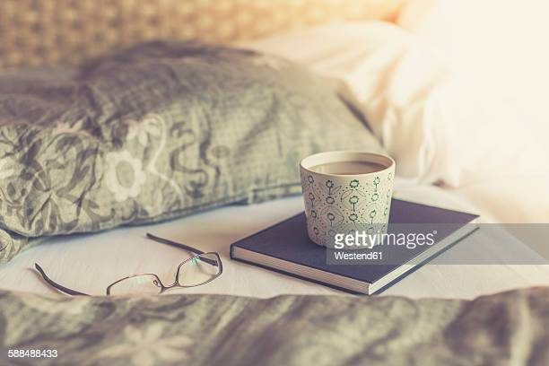 Book, reading glasses and cup of white coffee on bed