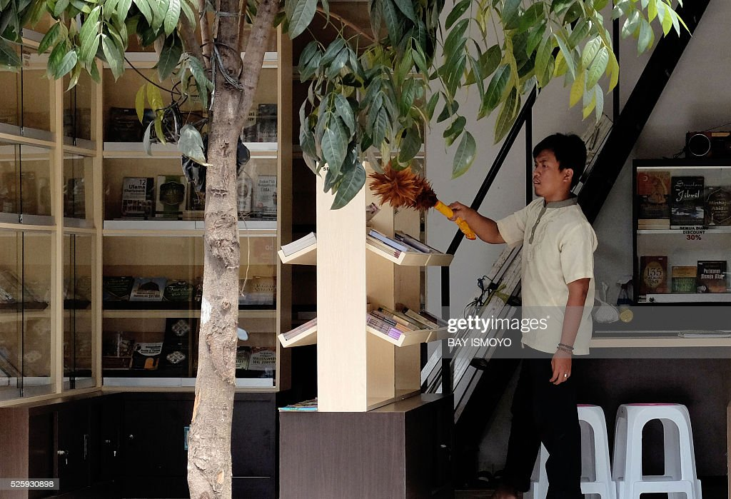 A book shop employee dusts as he opens for business in Jakarta on April 29, 2016. Indonesia's economy may recover more slowly than expected as the expansion of the manufacturing industry, which the government hopes will propel growth amid low private consumption, remains weak. / AFP / BAY