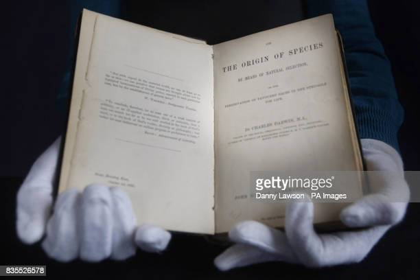 Book specialist Alex Dove holds a first edition of Charles Darwin's The Origin of Species that is to be auctioned at the Lyon and Turnbull auction...