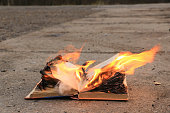 the book lies on the asphalt - the pages are burning with bright fire
