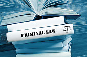 Law concept - Law book with Criminal Law  word on table in a courtroom or law enforcement office. Toned image.