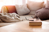 book with eyeglasses on wooden table in front of cozy couch