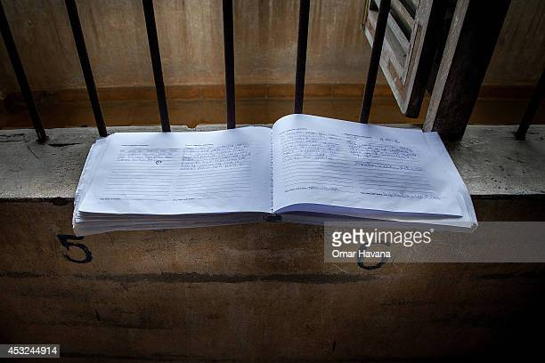 A book with messages from visitors to Tuol Sleng Prison is left by one of the windows of one of the torture rooms of the prison on August 6 2014 in...