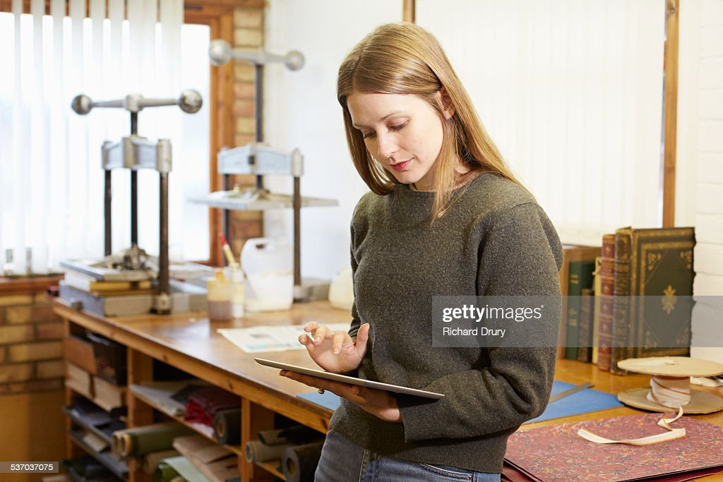 Bookbinder using digital tablet in her workshop
