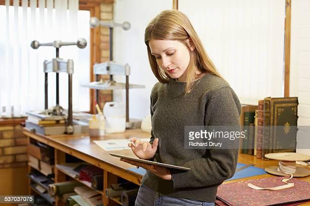 Bookbinder using digital tablet in her workshop