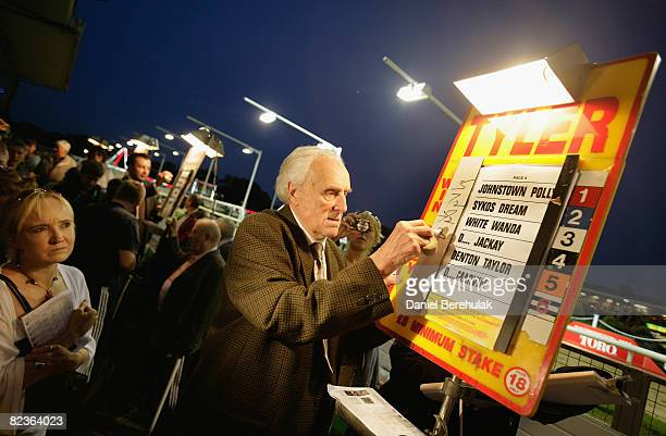 Bookie Douglas Tyler writes up the odds as punters look on during the second last night of racing at Walthamstow Greyhound Stadium on August 14 2008...