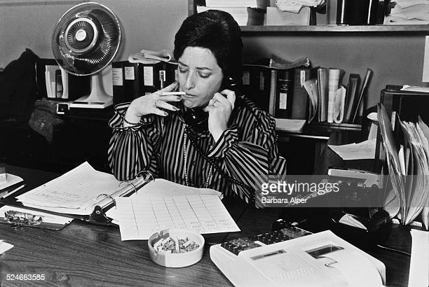 A bookkeeper smoking a cigarette at her desk while she works New York City USA 15th December 1982