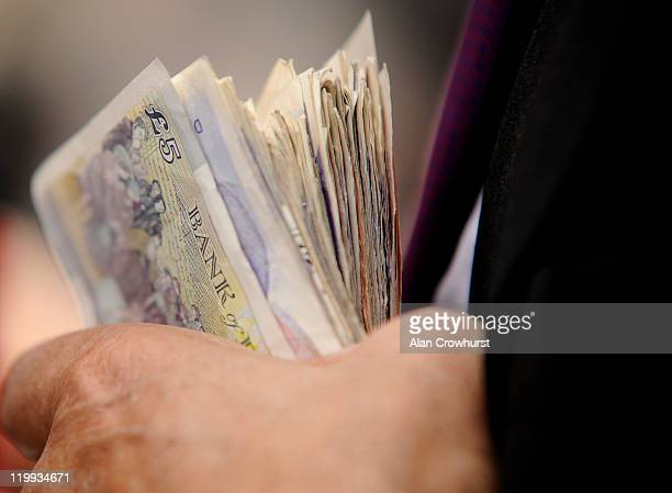A bookmaker holds bank notes at Goodwood racecourse on July 27 2011 in Chichester England