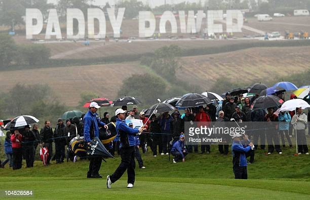 Bookmaker Paddy Power display a large sign on the hillside above the course as Rory McIlroy and Luke Donald of Europe hit shots during a practice...