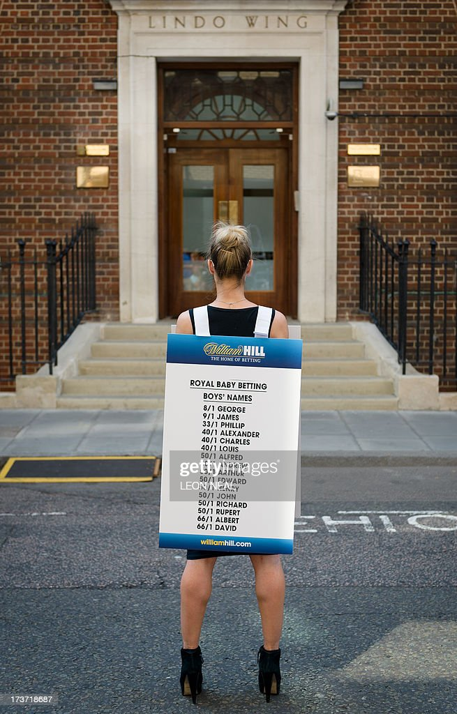 A bookmaker presents the latest odds on boys names outside the Lindo Wing of St Mary's Hospital in London, on July 17, 2013, where Prince William and his wife Catherine's baby is expected to be born. Britain's Prince Charles joked Monday that his son Prince William's baby was 'hopefully' on the way, but wife Camilla went further, saying it could arrive 'by the end of the week'. AFP PHOTO / LEON NEAL