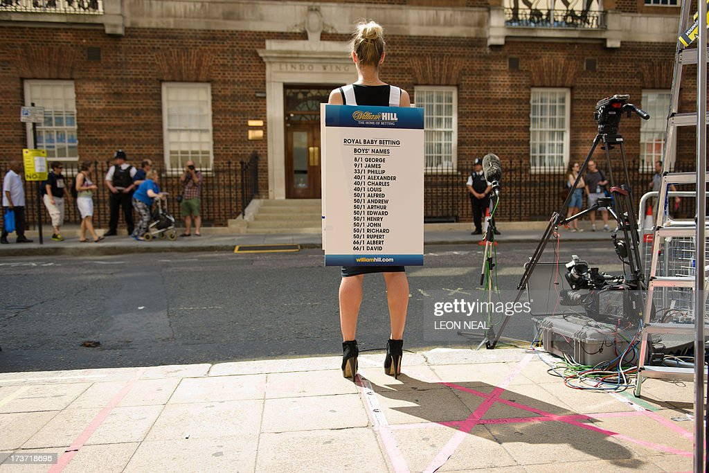 A bookmaker presents the latest odds on boys names outside the Lindo Wing of St Mary's Hospital in London, on July 17, 2013, where Prince William and his wife Catherine's baby is expected to be born. Britain's Prince Charles joked Monday that his son Prince William's baby was 'hopefully' on the way, but wife Camilla went further, saying it could arrive 'by the end of the week'.
