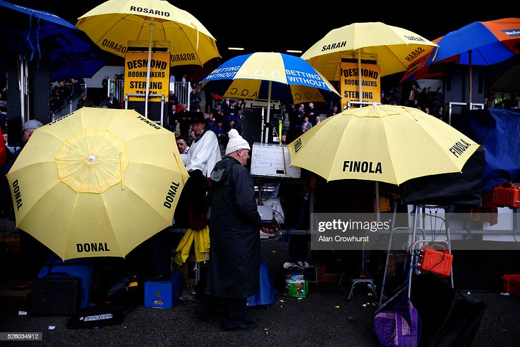 Bookmakers hold up yellow umbrellas at Punchestown racecourse on April 29, 2016 in Naas, Ireland.