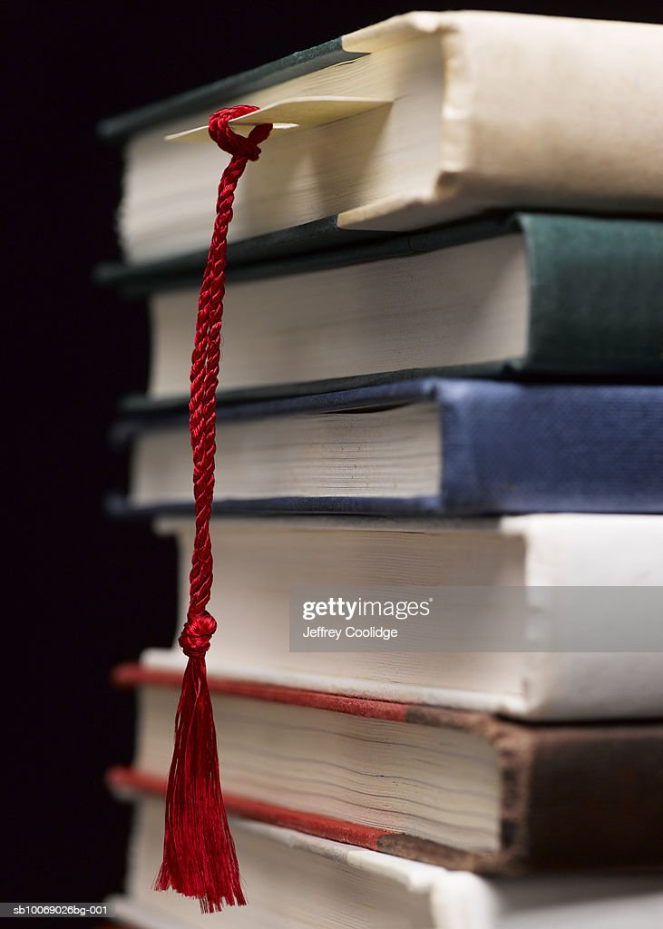 Bookmark dangling from stack of books, close-up : Stock Photo