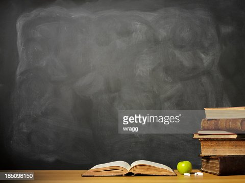 Books and apple on a desk in front of chalkboard