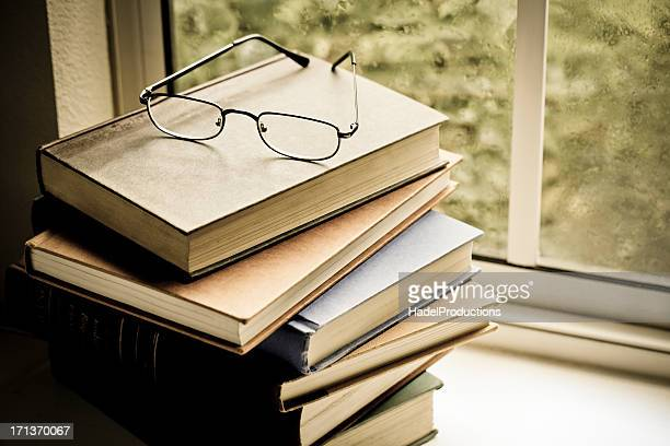 Books and eyeglasses on shelf by window